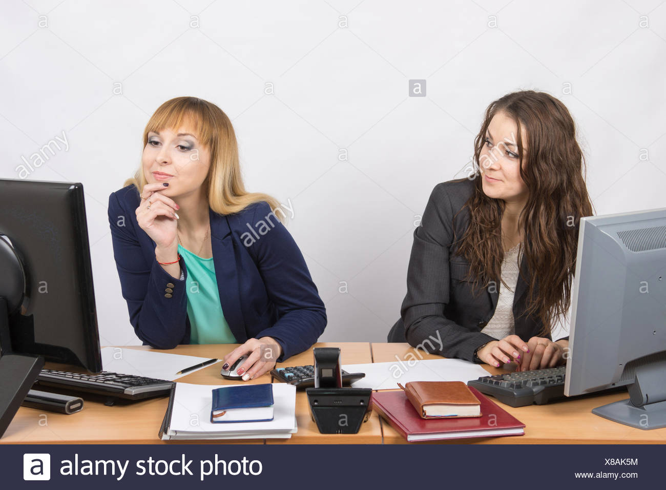Office worker looking with distaste at the colleague sitting next to staring at a computer monitor - Stock Image