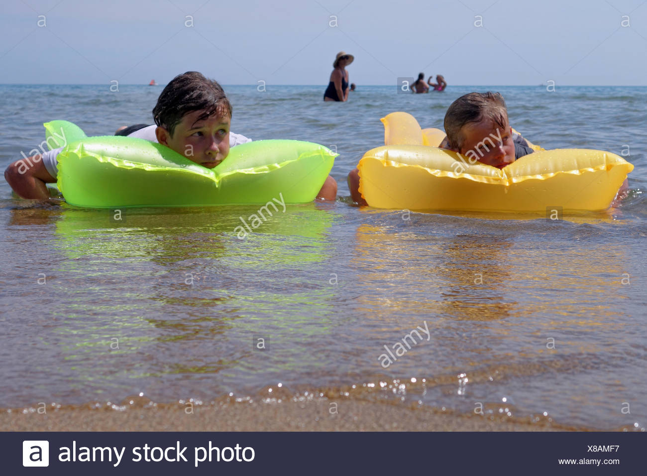 Populonia, Italy, two boys are bored on their air mattresses in the sea - Stock Image