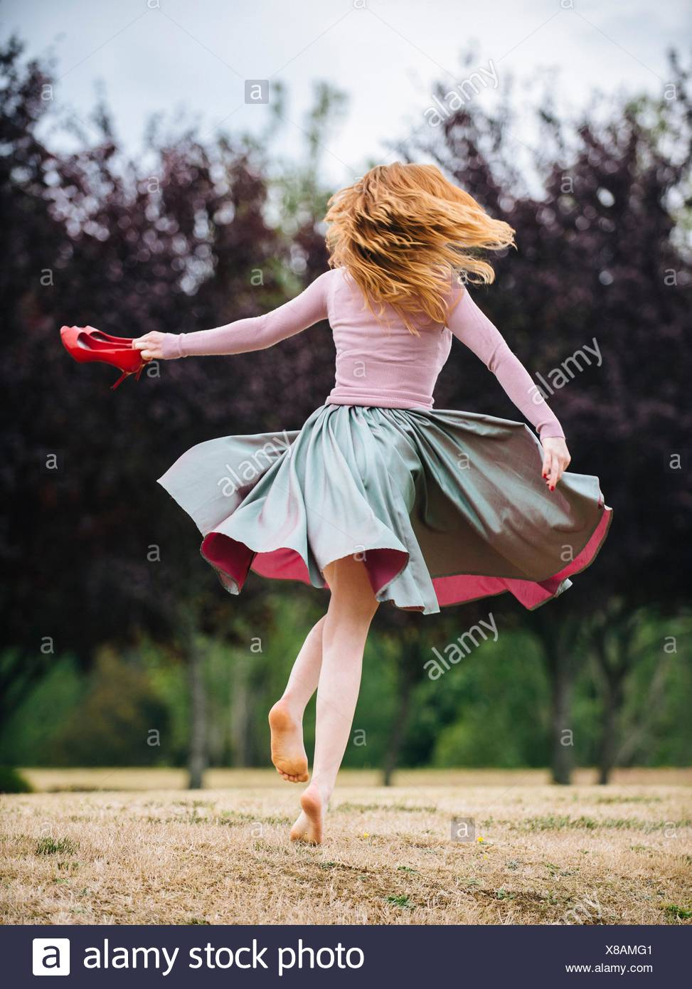Rear view of young woman dancing and twirling and in park - Stock Image