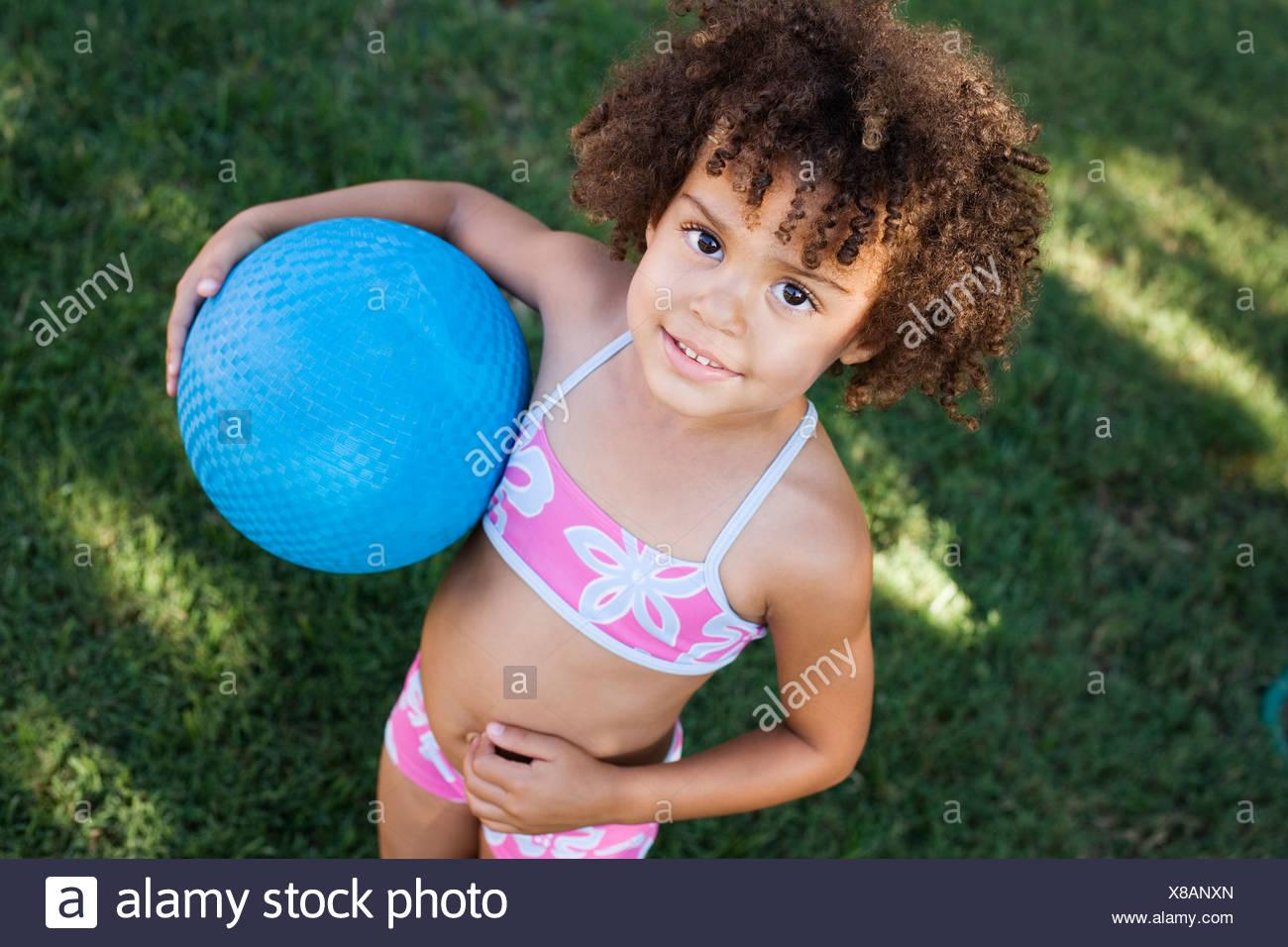 Girl in swimwear holding ball in yard - Stock Image