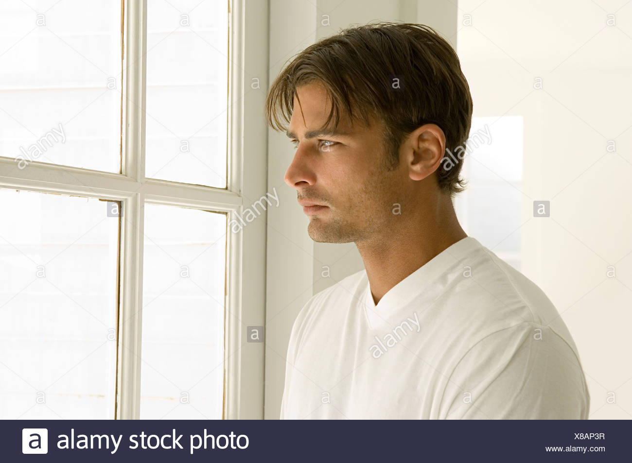 Man looking out of window - Stock Image