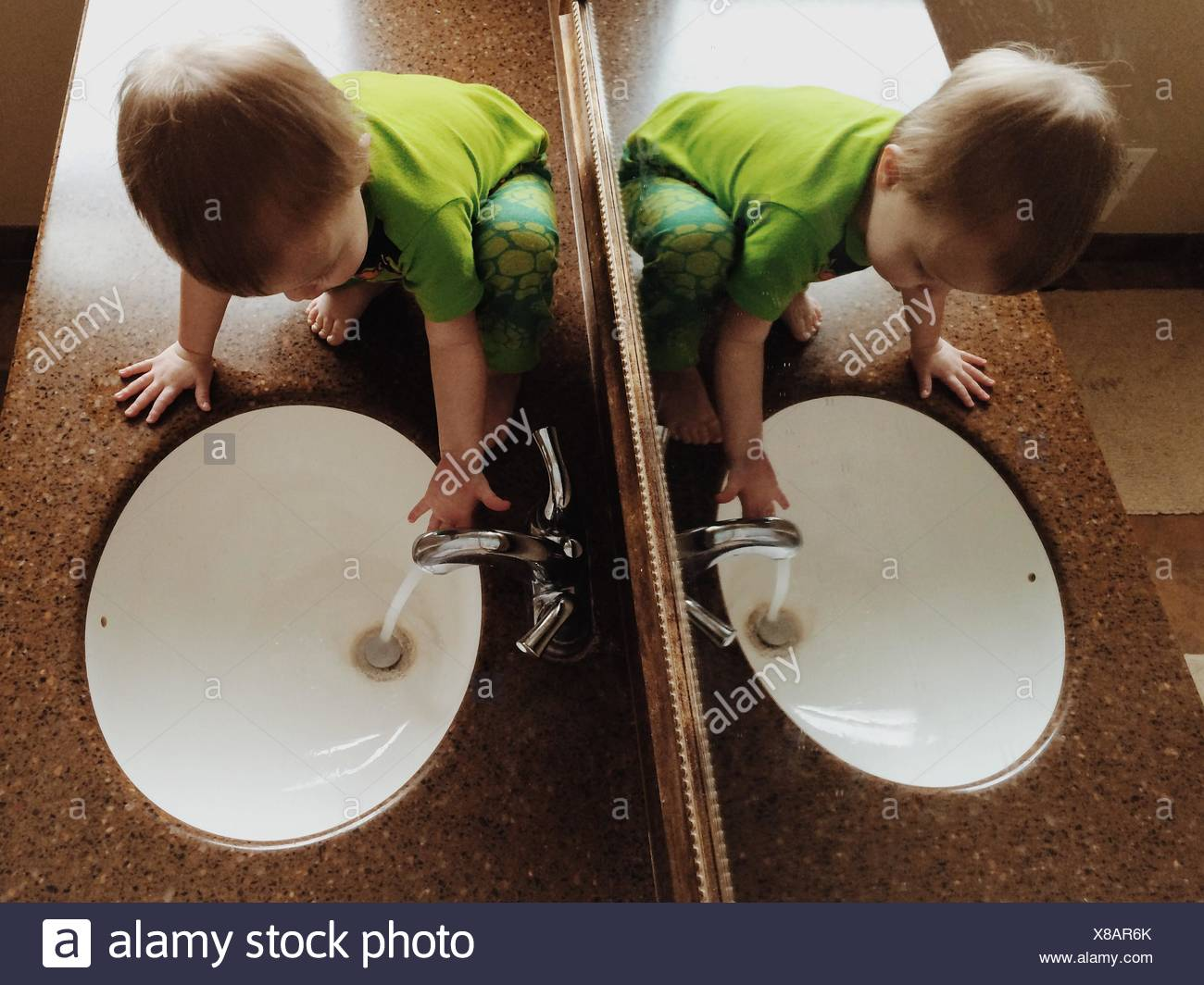 Boy Playing In Water In Bathroom Sink - Stock Image