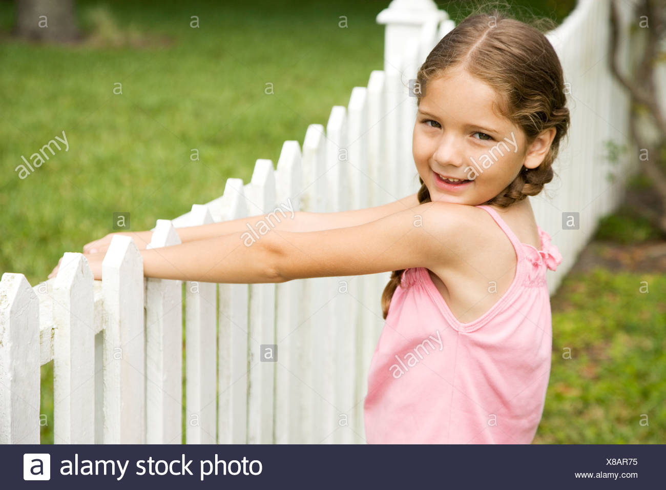 little girl standing by picket fence - Stock Image