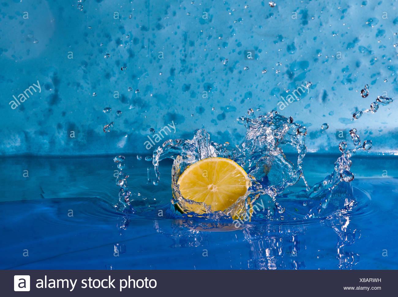 Lemon splashing into water - Stock Image