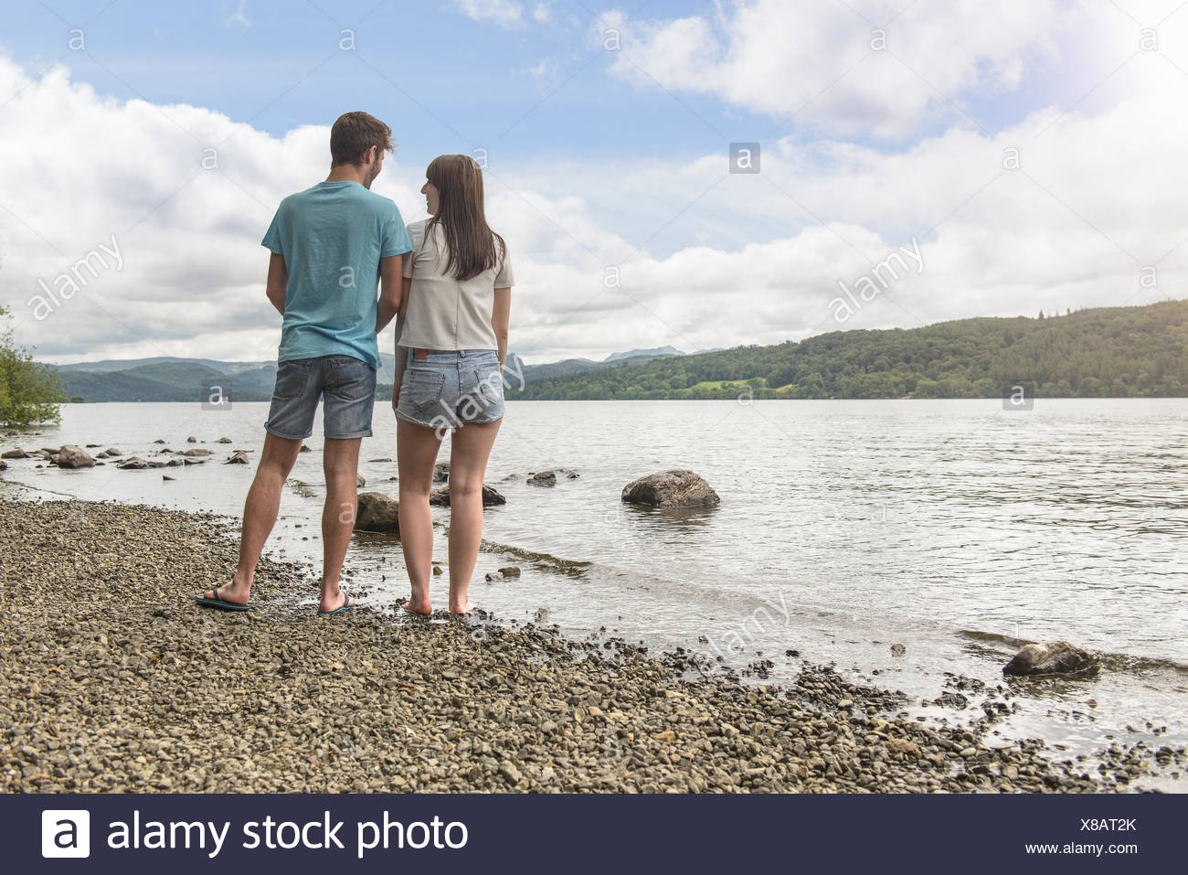Young couple looking to each other at the edge of lake under sunny sky - Stock Image