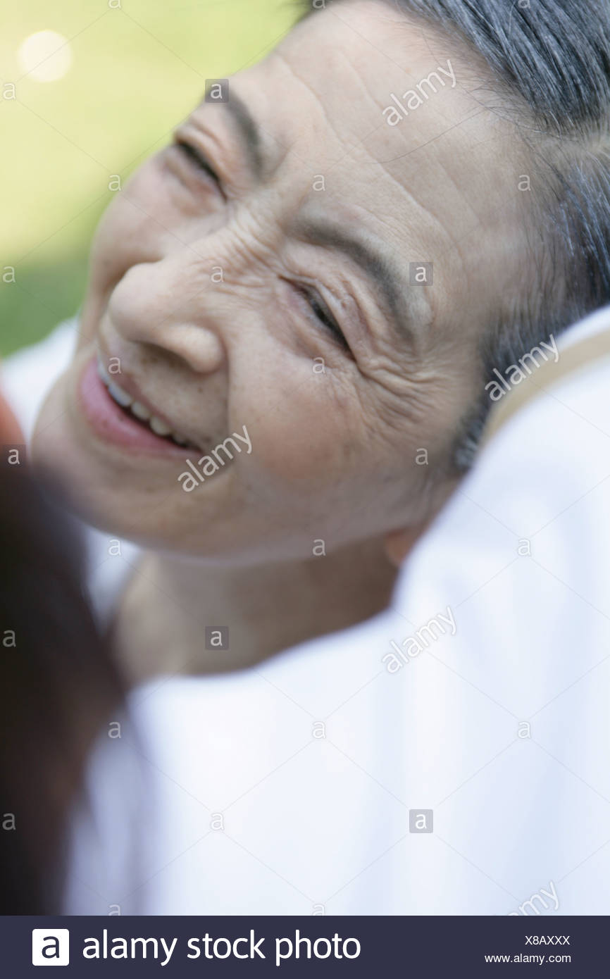 Person bending over senior woman outdoors, close-up - Stock Image