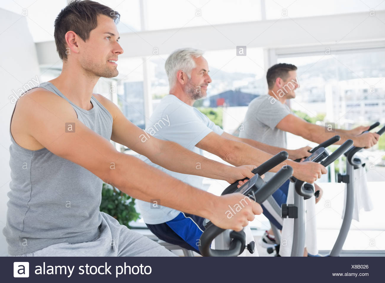 Men working out on exercise machines - Stock Image
