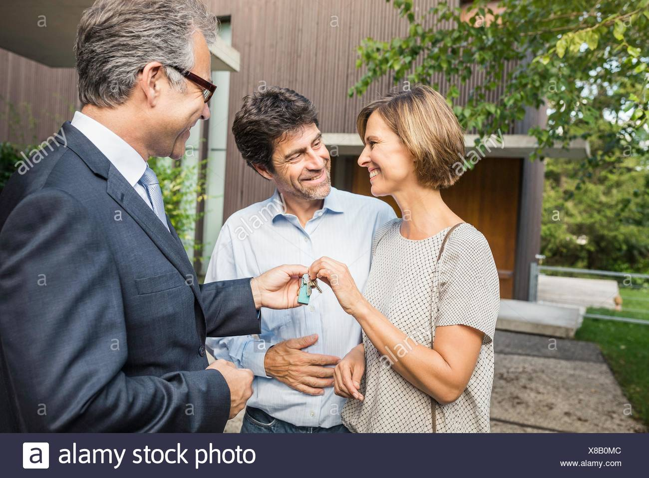 Estate agent handing keys to mature couple at new house - Stock Image