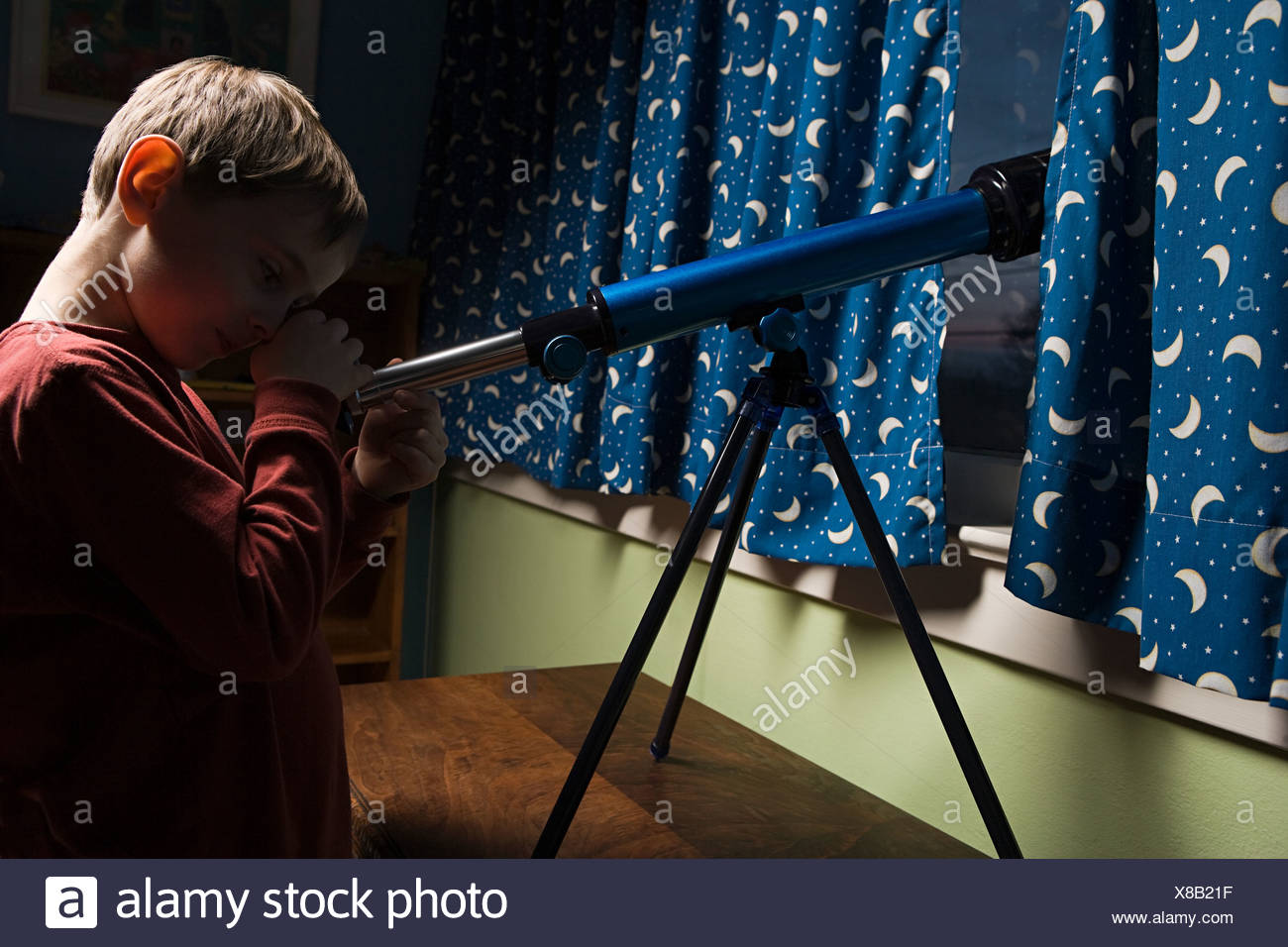 Boy looking through a telescope - Stock Image