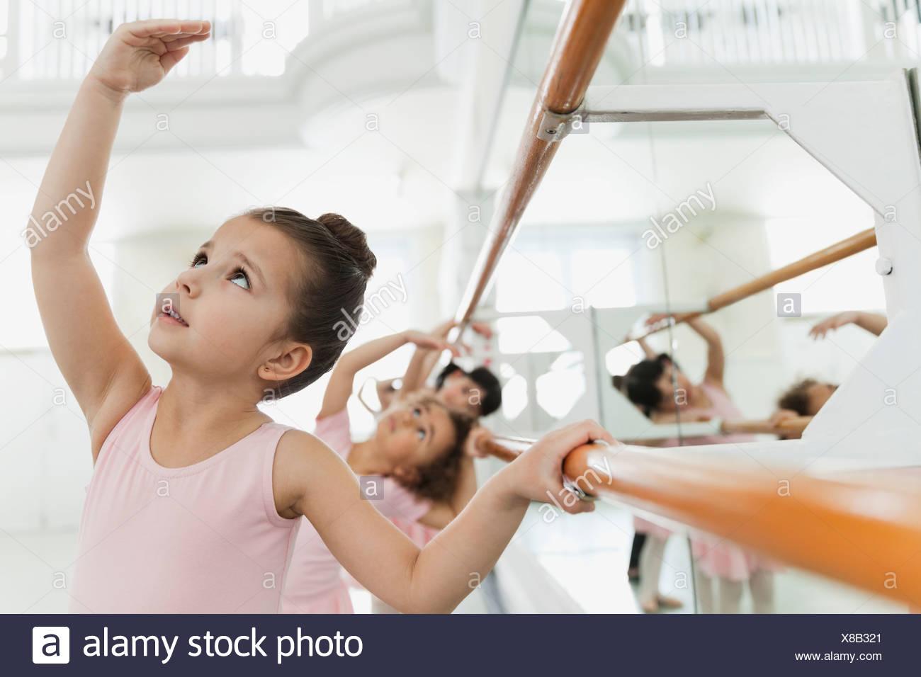 Children practicing ballet poses in ballet studio - Stock Image