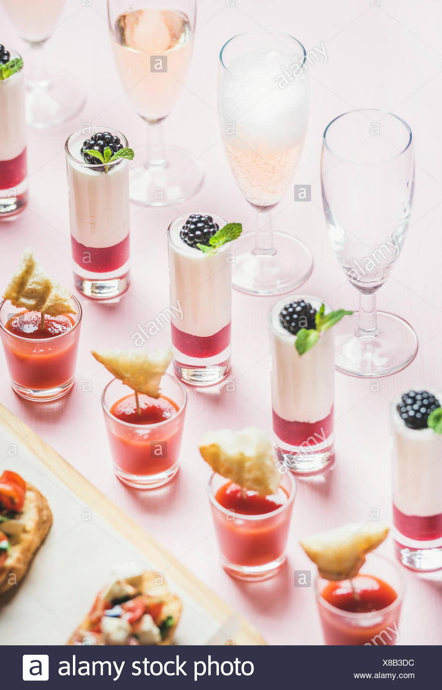 Close-up of various snacks, brushettas, gazpacho shots, desserts with berries and champagne on corporate event, christmas, birthday, wedding celebrati - Stock Image