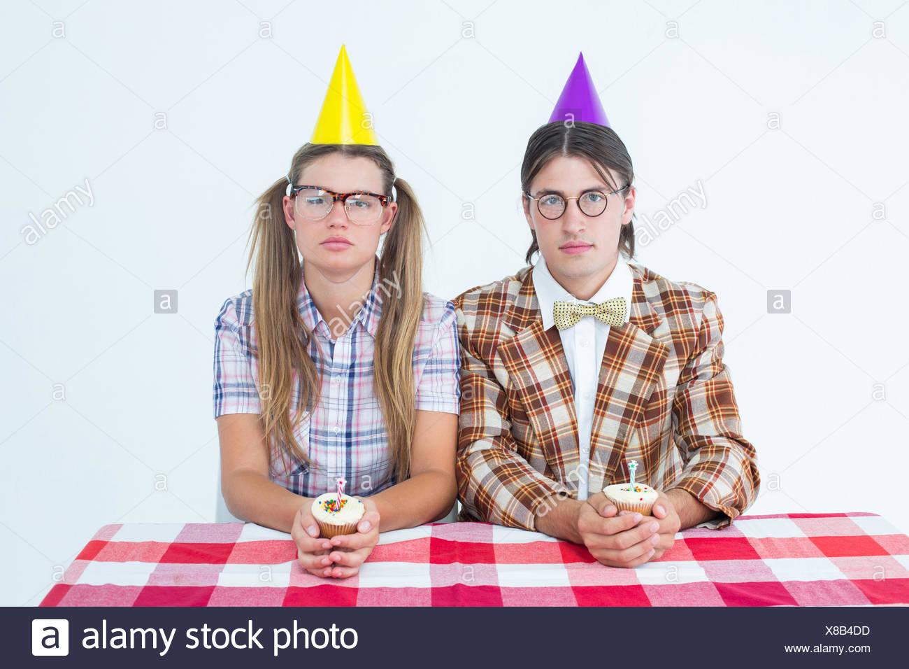 Unsmiling geeky hipsters celebrating birthday - Stock Image
