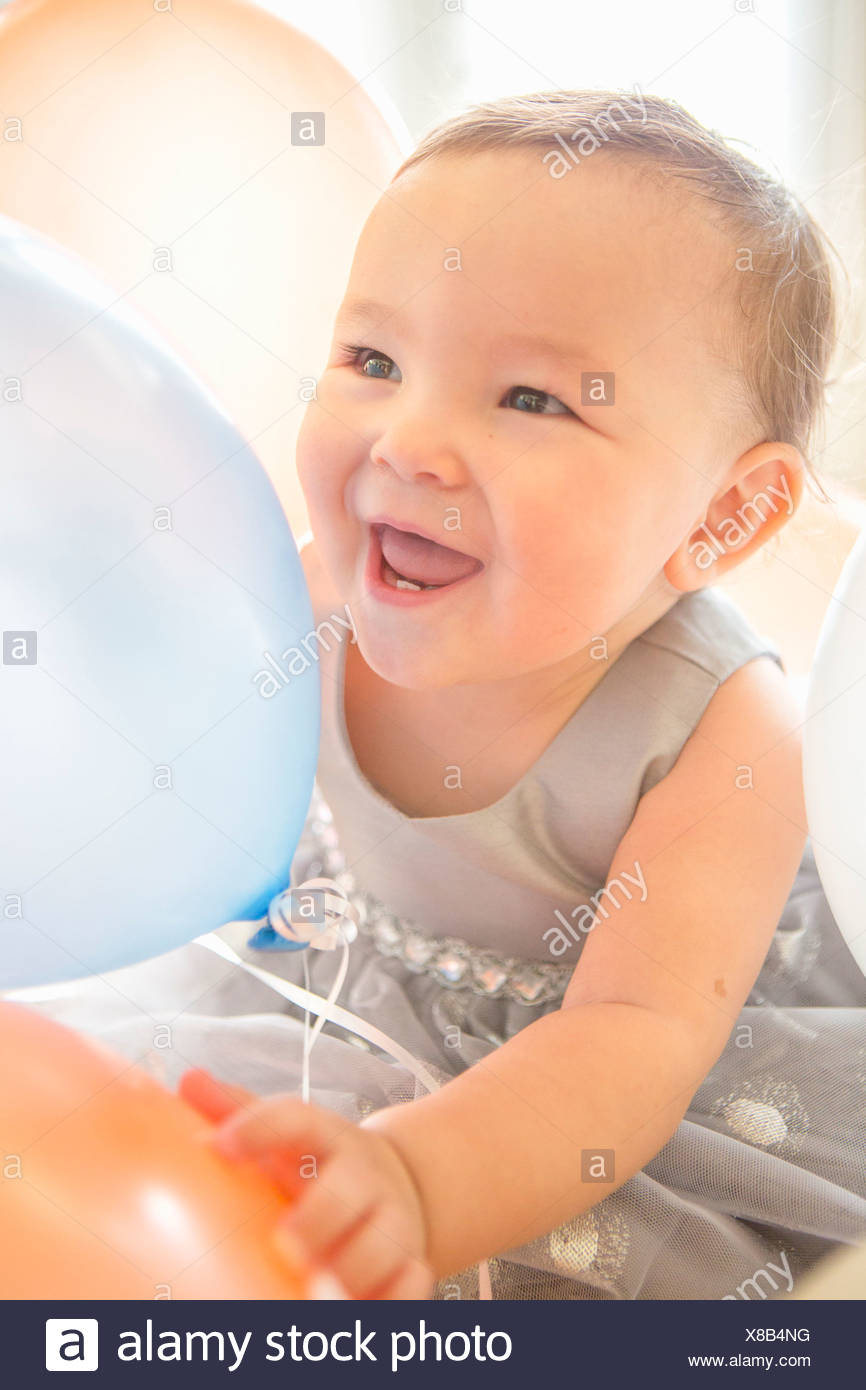 Baby girl wearing party dress with balloon - Stock Image