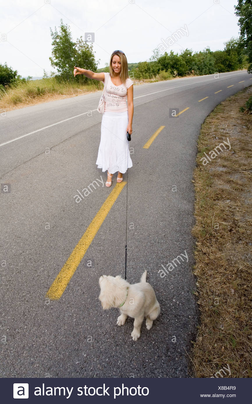 Young lady in white and her disobedient pet dog - Stock Image