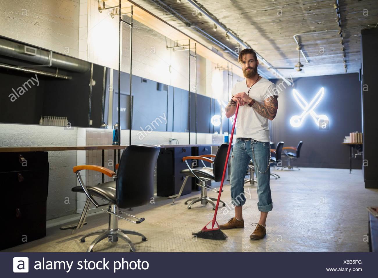 Portrait hipster hairstylist sweeping hair salon floor broom - Stock Image
