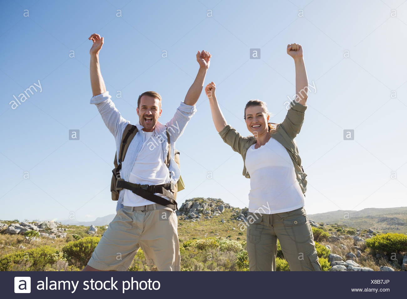 Hiking couple cheering at camera on mountain terrain - Stock Image