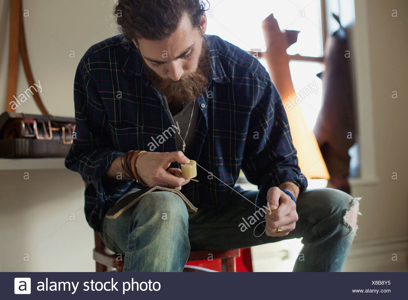 Young man with wax cube and string at workshop - Stock Image