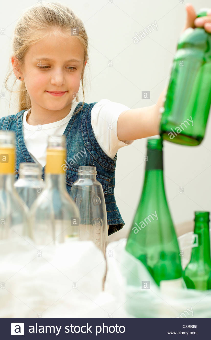 Girl separating green plastic bottle clear glass bottle, Den Haag, Netherlands - Stock Image
