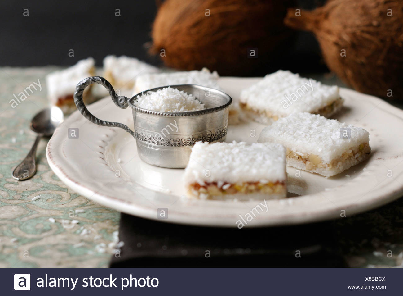 Coconut and cherry slices on a white plate - Stock Image