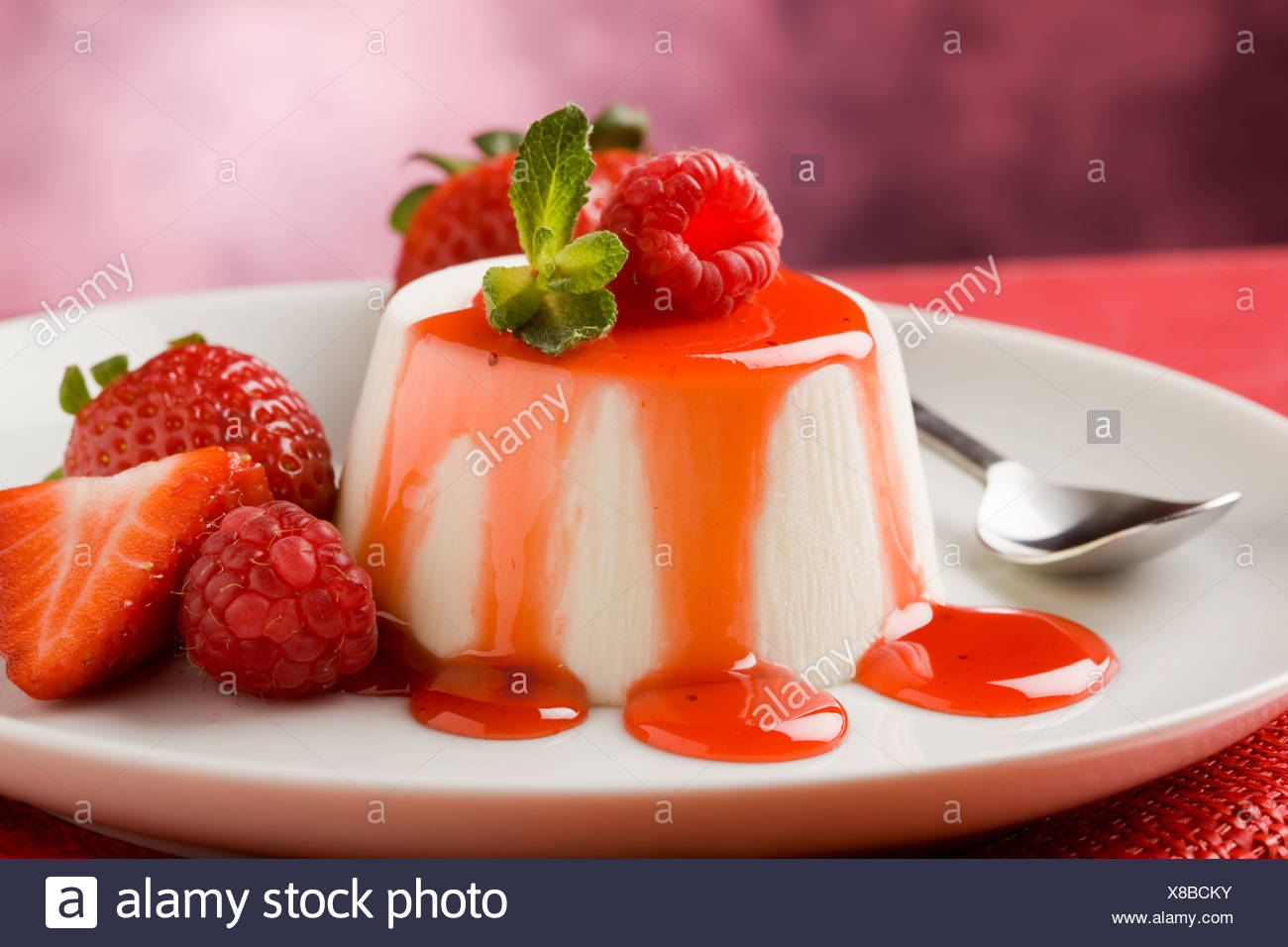 photo of italian panna cotta dessert with strawberry sirup and mint leaf - Stock Image