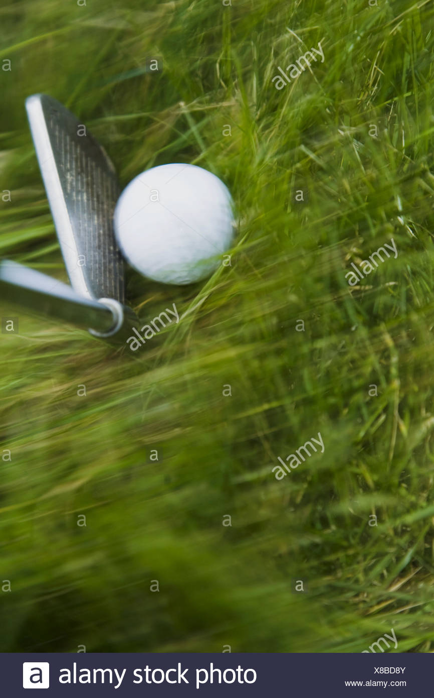 GOLF Blurred motion of club and golf ball in heavy grass on course in Deerfield, Illinois - Stock Image