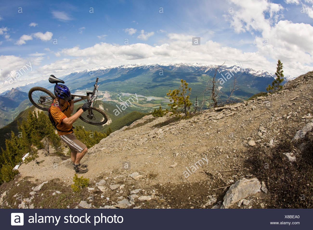 Middle aged man carries his mountain bike up Mt. Seven for an epic descent. Golden, BC - Stock Image