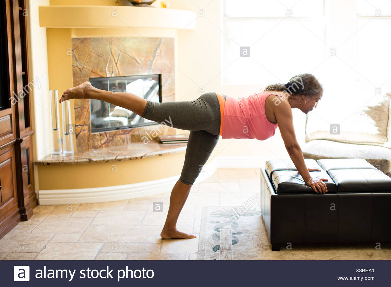 Side view of woman leaning against pouffe doing stretching exercise - Stock Image
