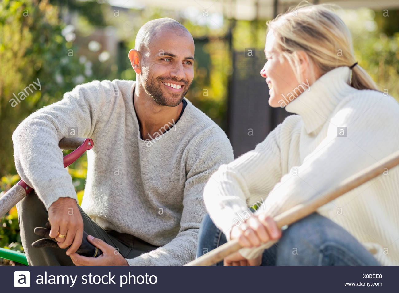 Mature couple with gardening equipment sitting at yard - Stock Image