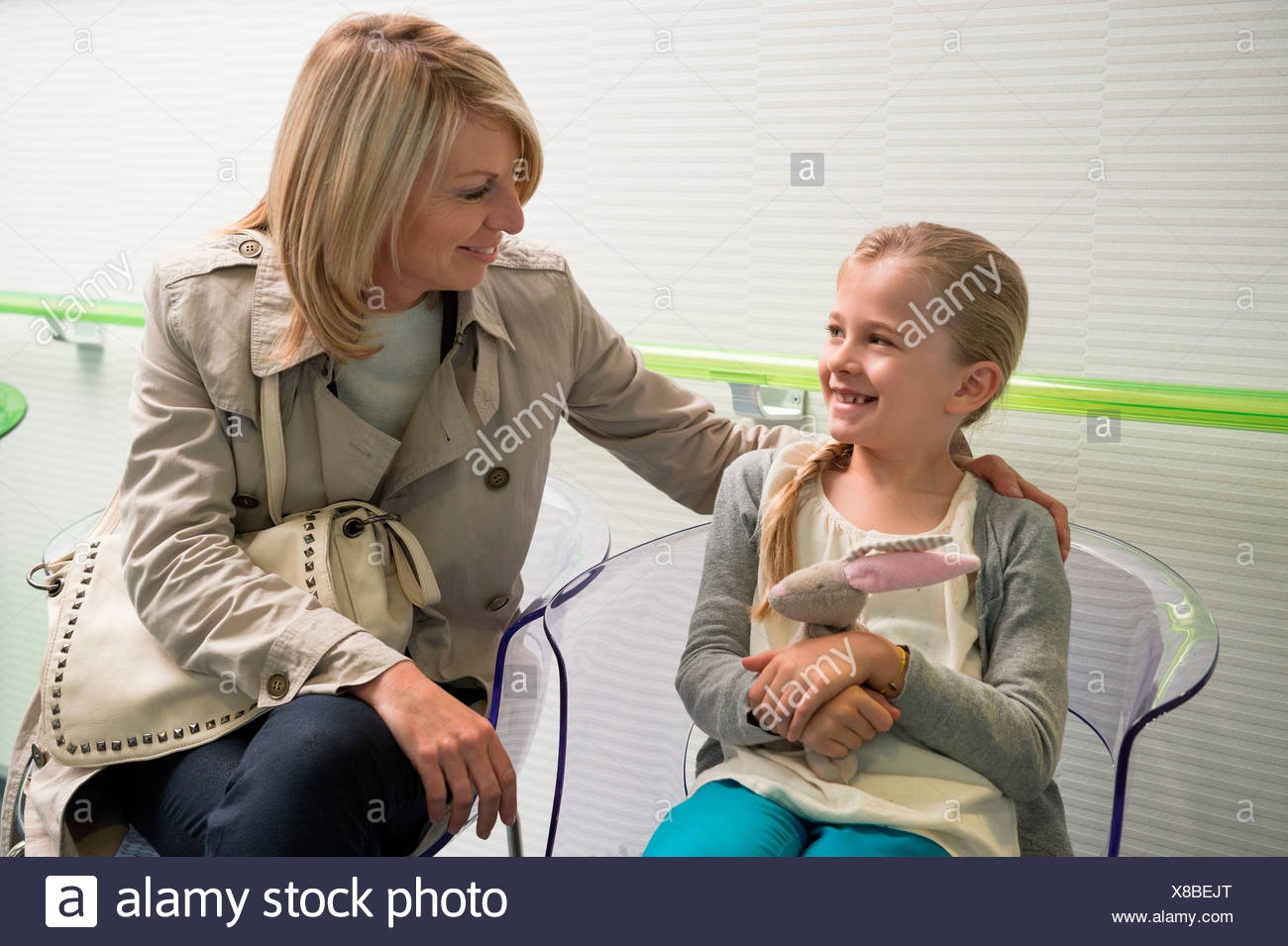 Woman with her daughter sitting in hospital waiting room - Stock Image