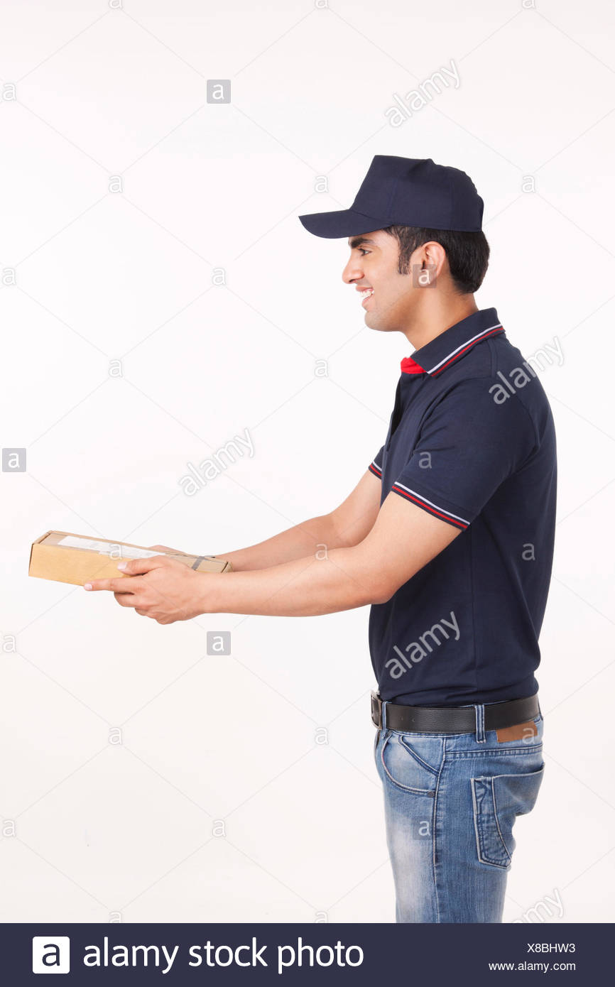 Profile shot of delivery man giving package against white background - Stock Image