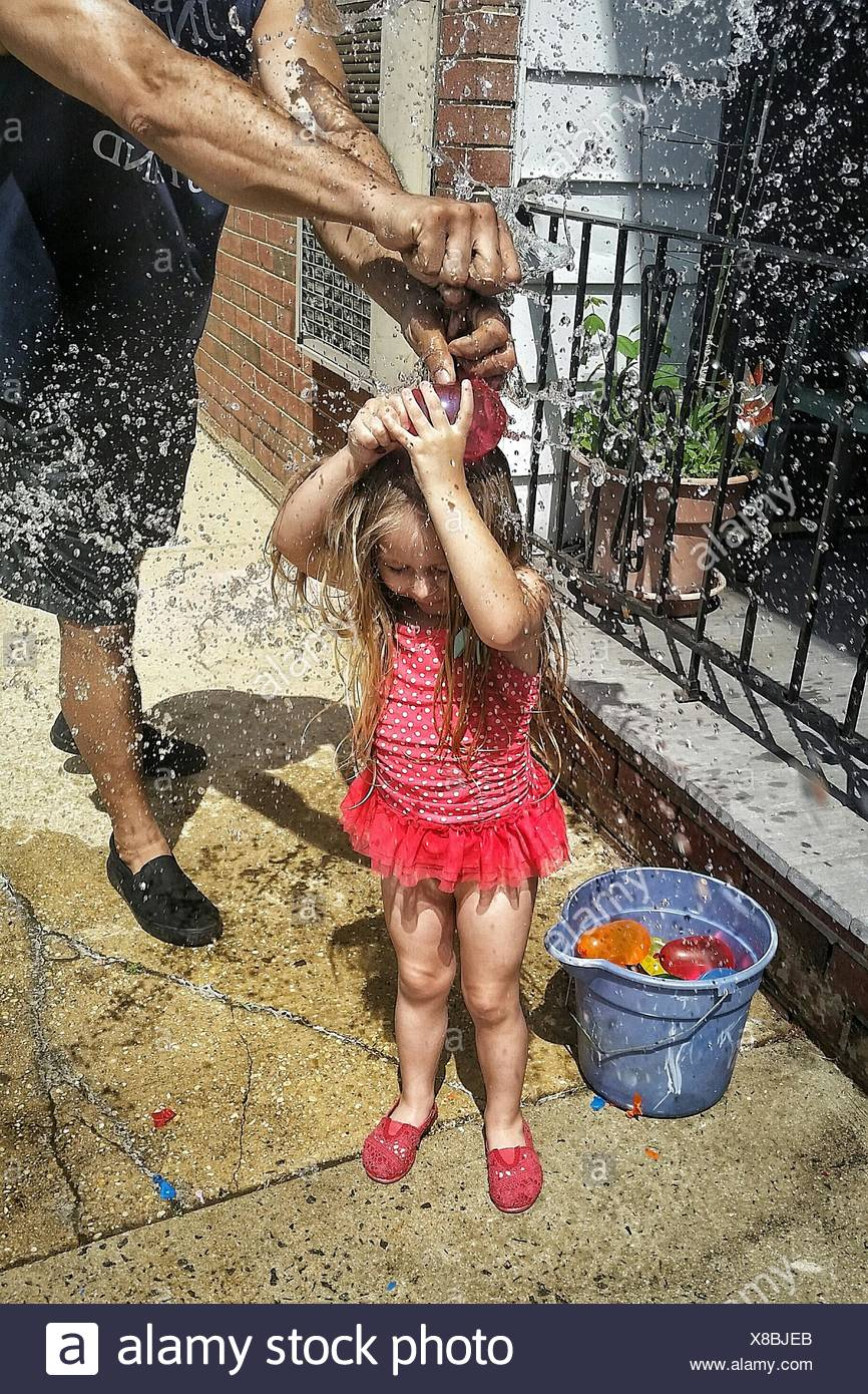 Cropped Image Of Man Playing Water Bomb With Daughter - Stock Image