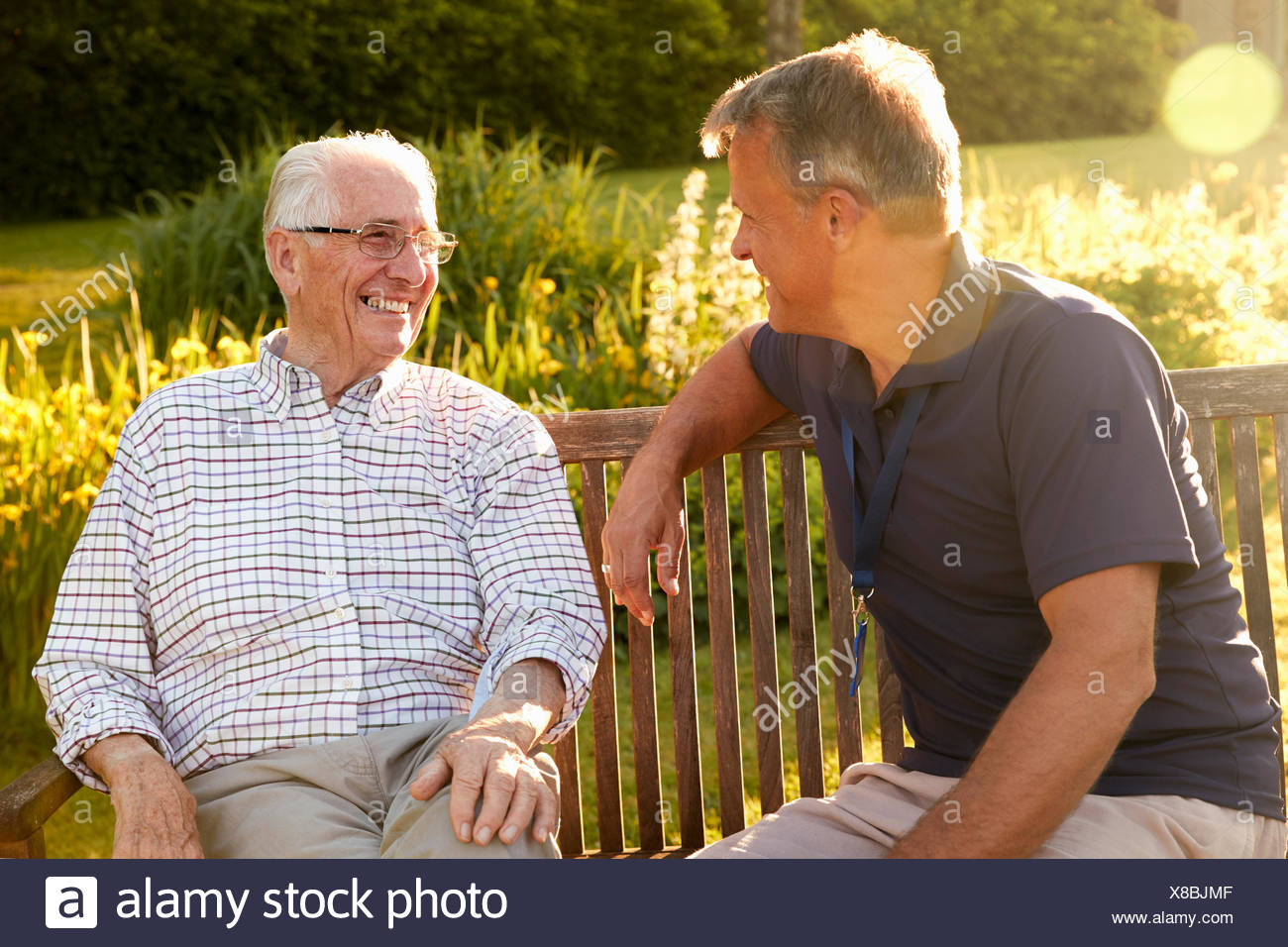 Man Visiting Senior Male Relative In Assisted Living Facility - Stock Image