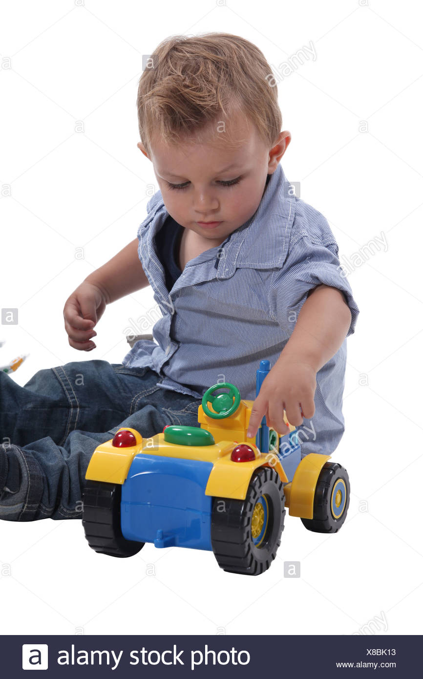 Young boy playing with a toy car - Stock Image