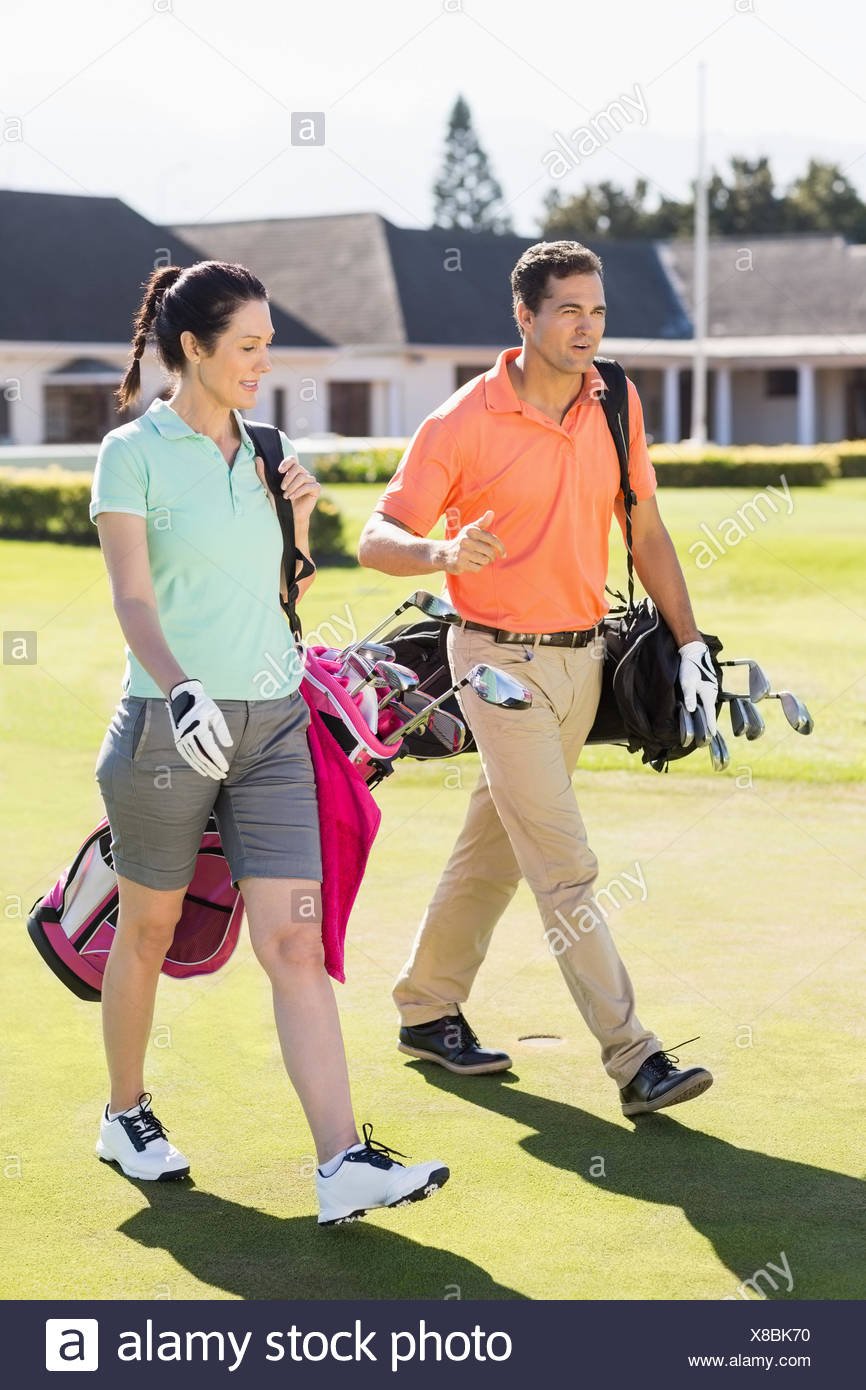 Full length of couple carrying golf bags - Stock Image