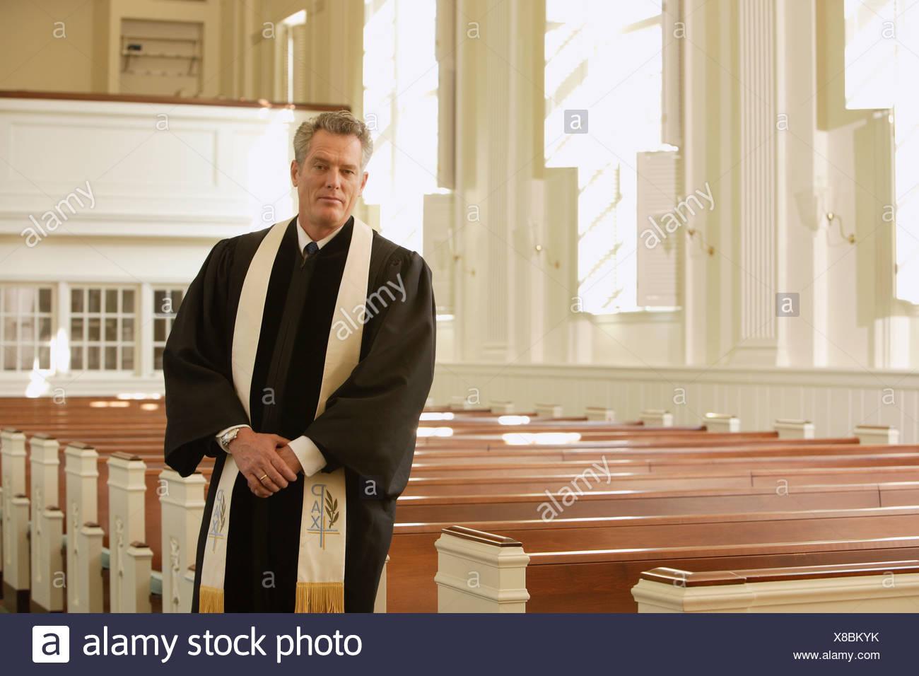 Priest standing next to pews Stock Photo