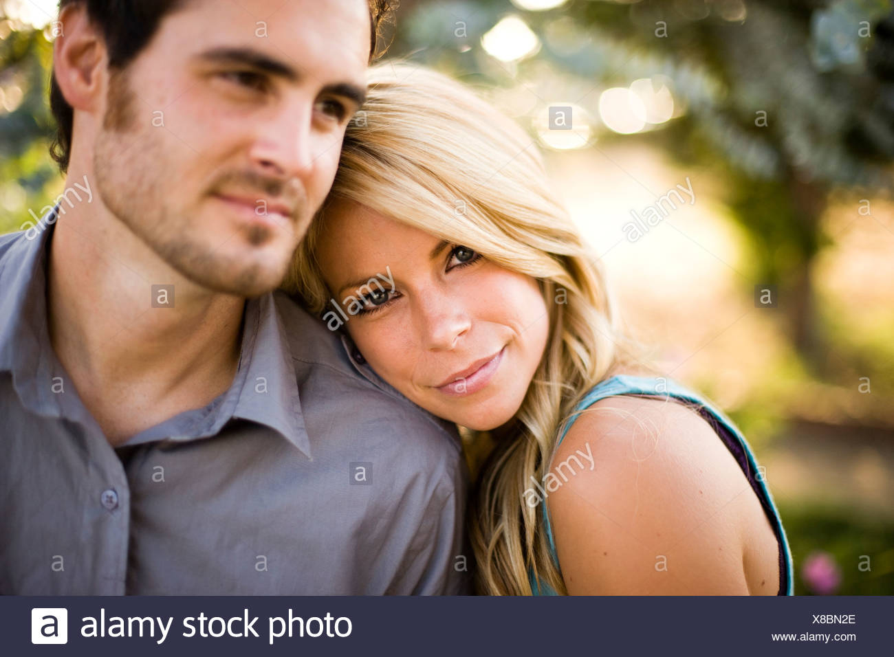 Portrait of woman leaning on man's shoulder - Stock Image