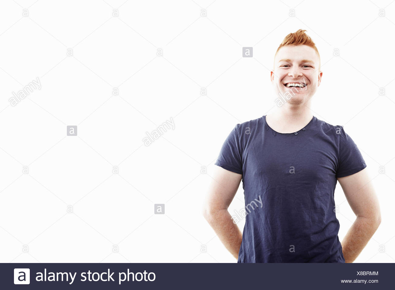 Studio portrait of young man smiling - Stock Image