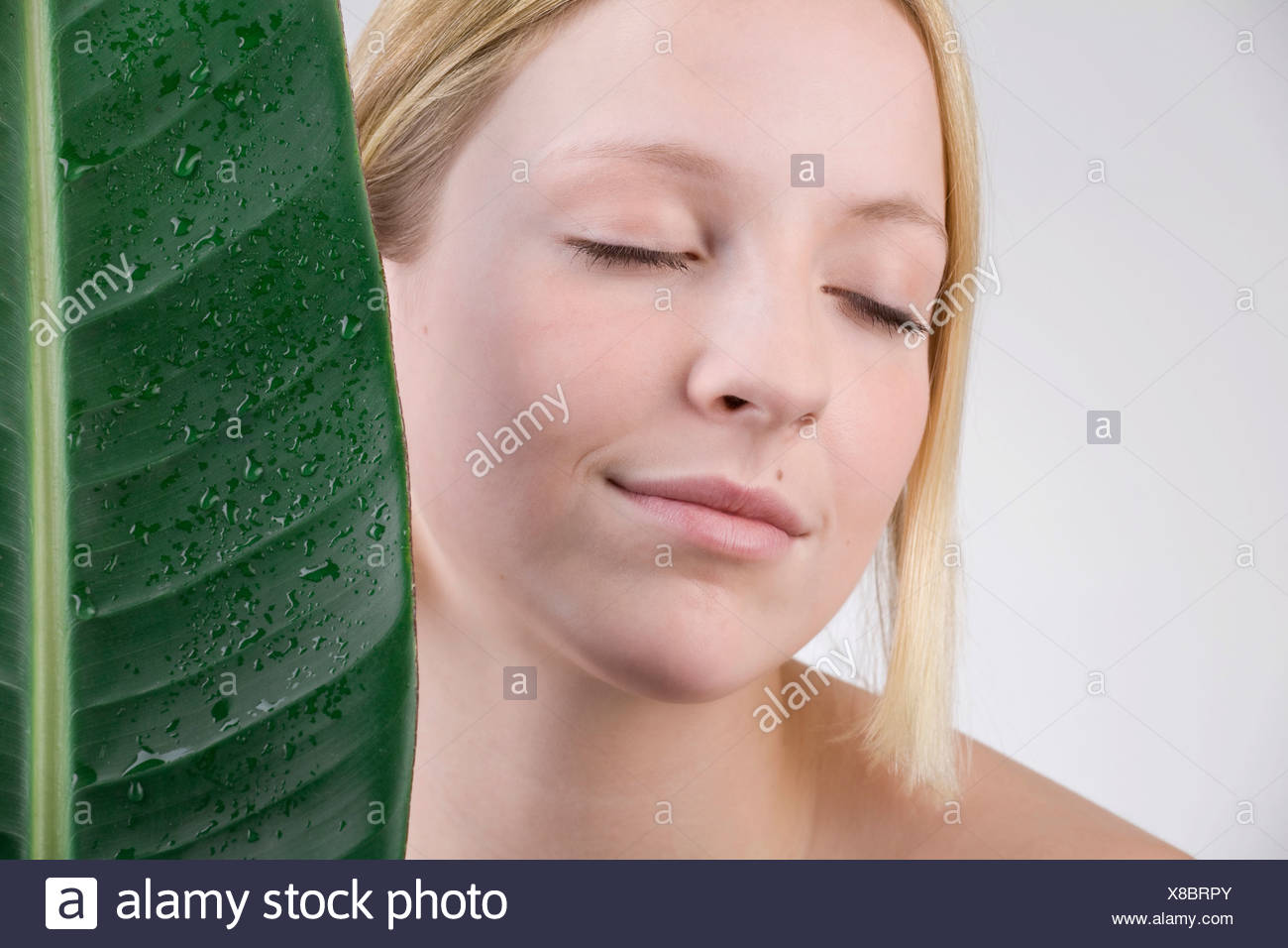Young woman next to a leaf, moisture and sensitive skin - Stock Image