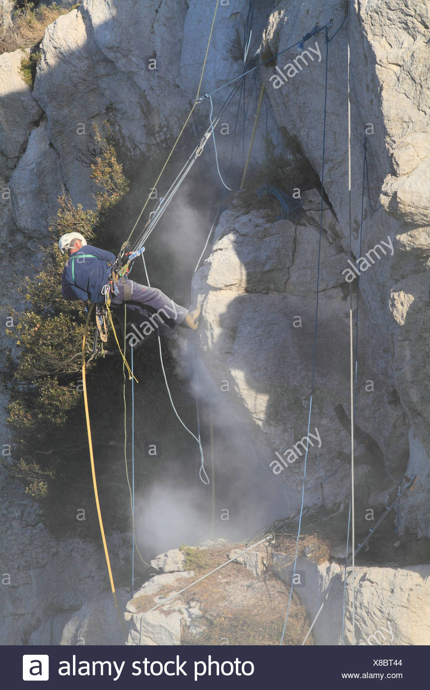 Workers safeguarding a cliff with jackhammers against landslides, loose rock is blasted off, La Turbie above Monaco, Département - Stock Image
