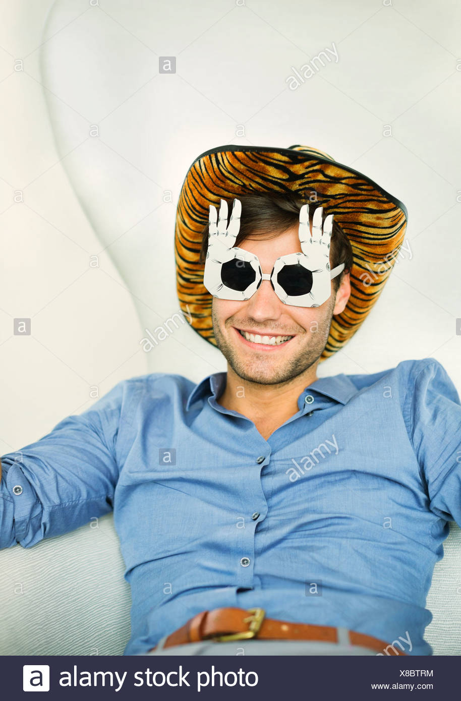 Smiling man wearing silly glasses - Stock Image