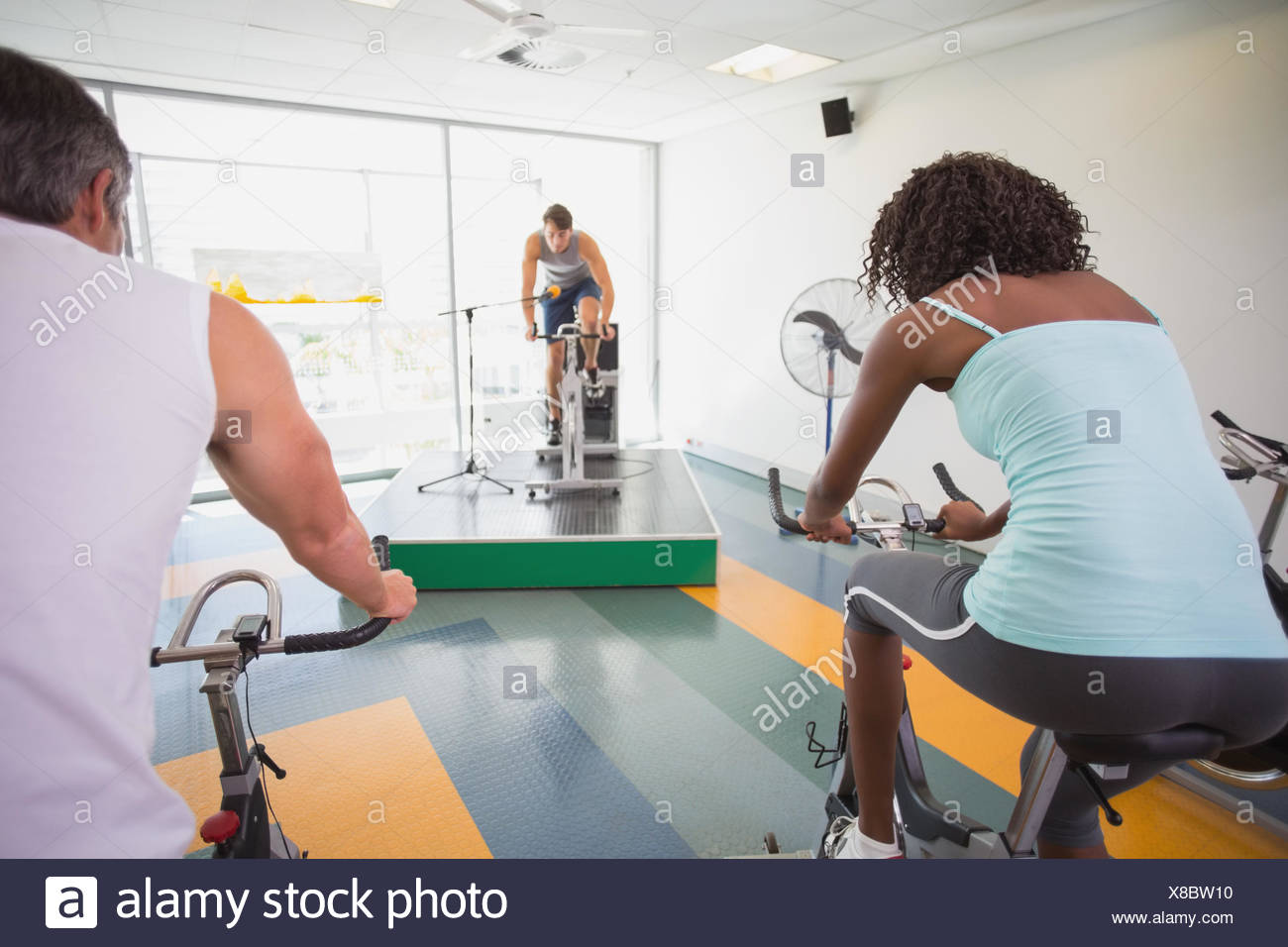 Spin class working out with motivational instructor Stock Photo