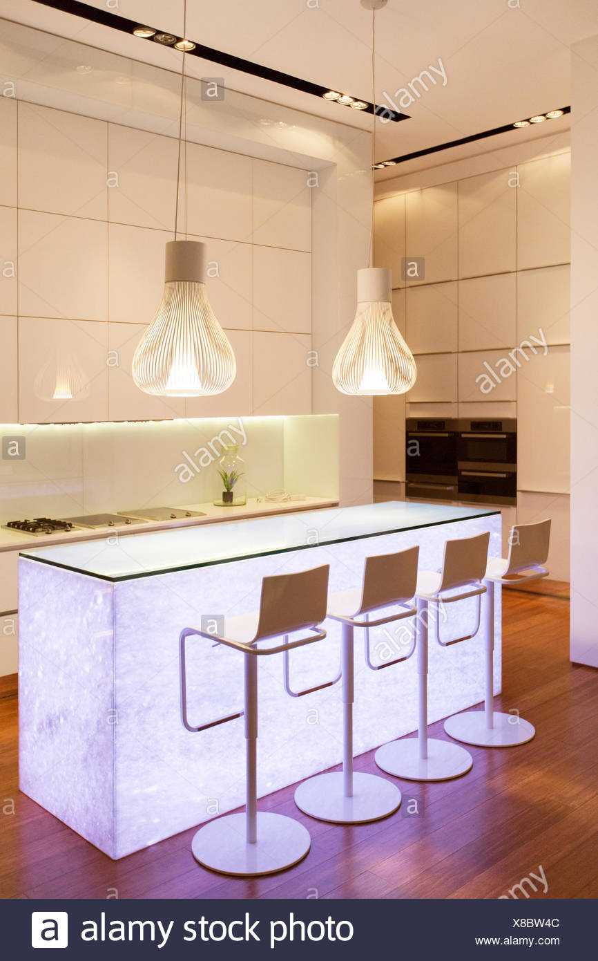 Bar stools and light features in modern kitchen - Stock Image