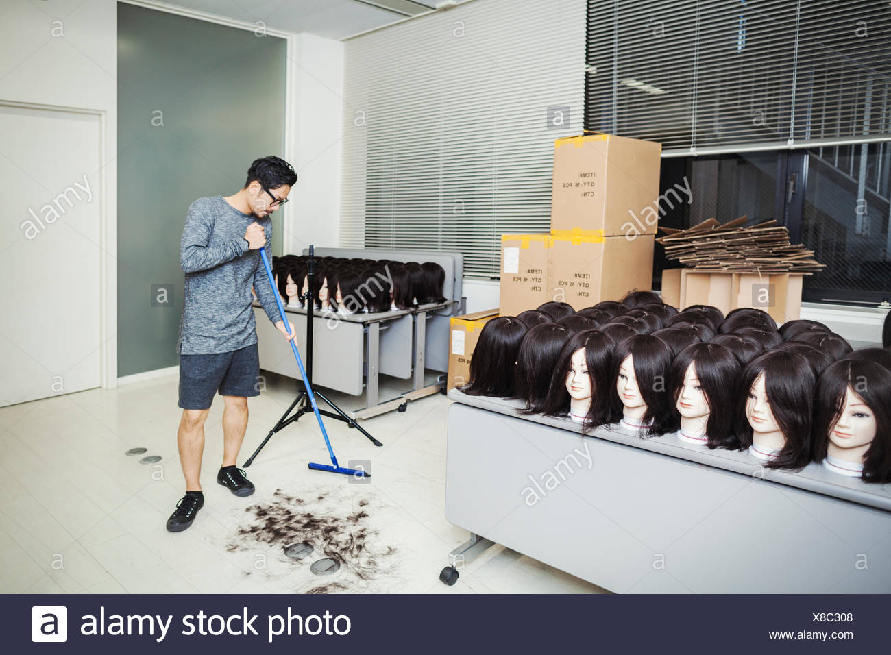 Bearded man wearing glasses standing indoors, sweeping hair on floor, large group of mannequin heads with brown wigs on tables. - Stock Image