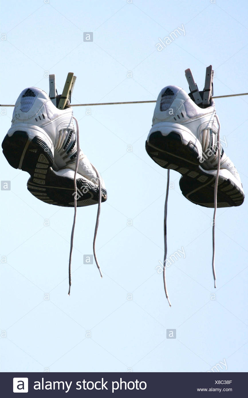 two gym shoes at a clothesline - Stock Image