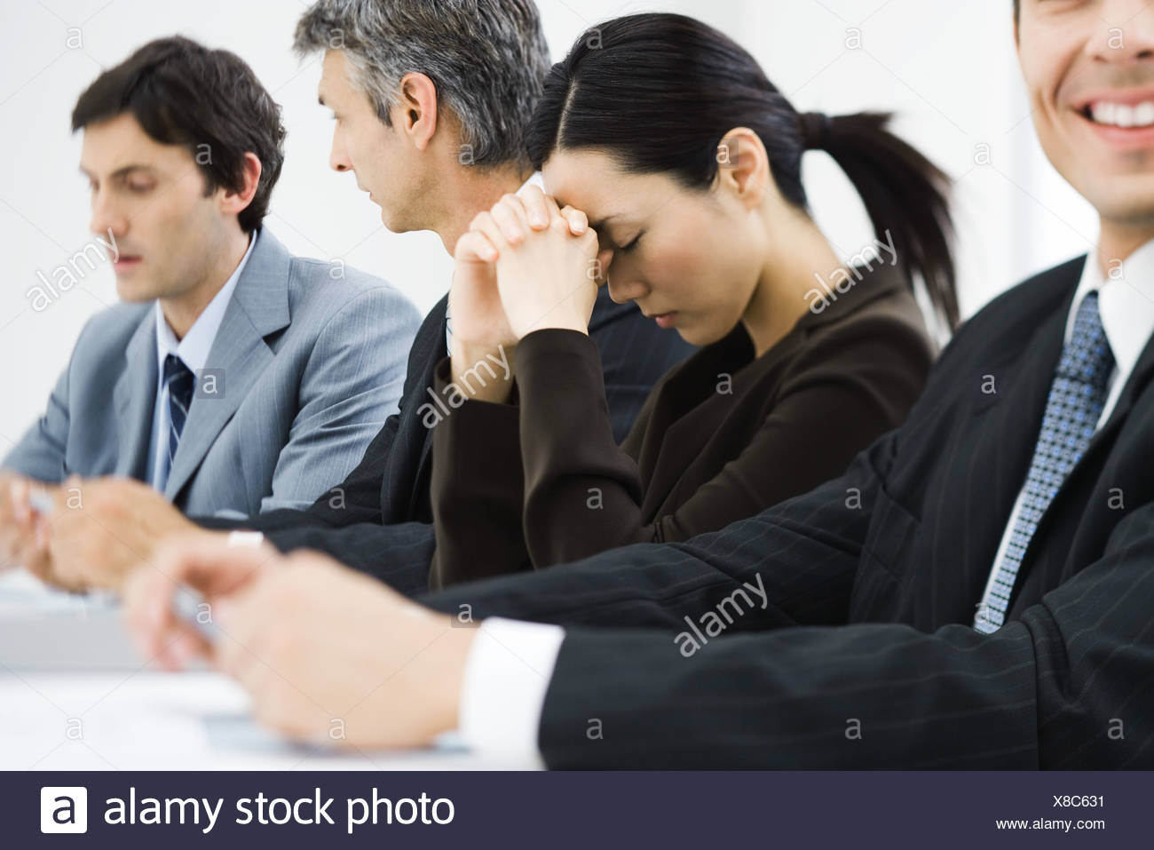 Executives in business meeting, woman closing eyes and leaning head against hands - Stock Image