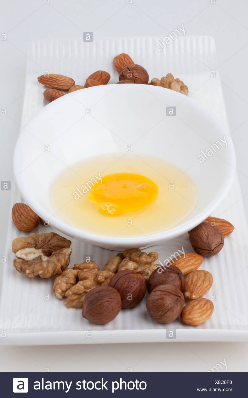 Cracked Raw Egg and Mixed Nuts - Stock Image