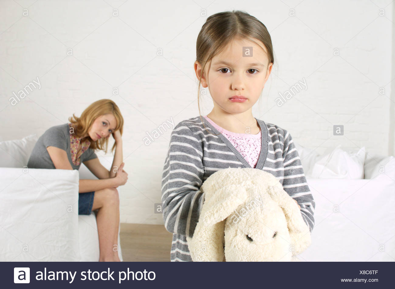 Cheerless girl looking at camera, mother sitting in background - Stock Image