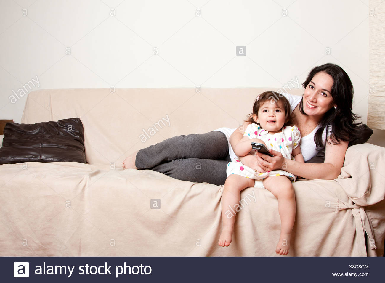 Beautiful happy family mother and baby toddler daughter sitting relaxed laid back on sofa couch in livingroom watching TV - Stock Image