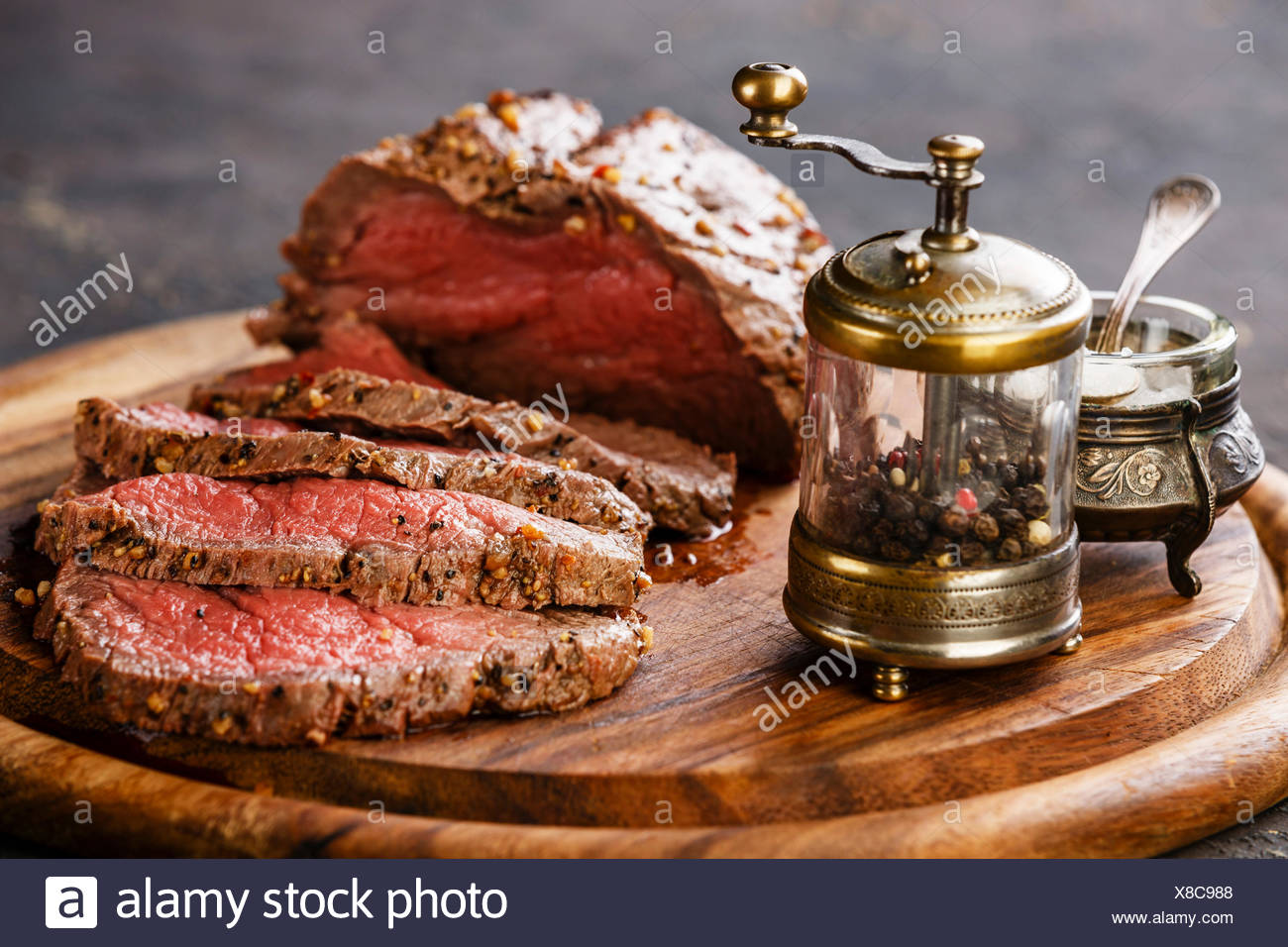 Roast beef on cutting board with saltcellar and pepper mill - Stock Image