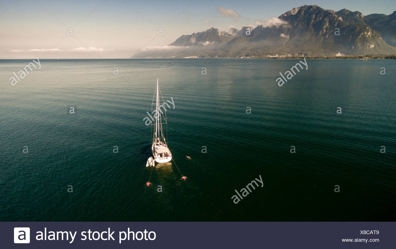 sailing boat anchored in the Geneva Lake in Vaud Canton on a beautiful day with mountains in the background and blue sky. - Stock Image